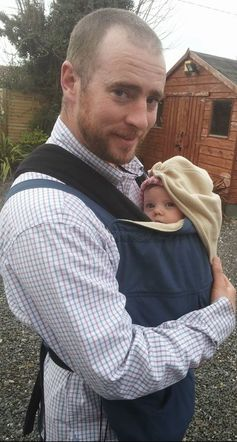 My husband carrying our daughter in a sling covered by a babywearing cover on a spring day