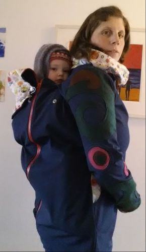 Photo of me wearing my daughter in a sling in a back carry inside a waterproof babywearing jacket.